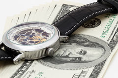 100 dólares no fundo branco com relógios de pulso Imagens de Stock