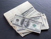 Dólares no fundo de pedra preto Fotos de Stock
