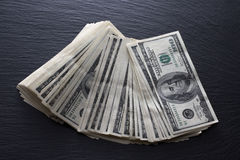 Dólares no fundo preto da rocha Fotografia de Stock Royalty Free