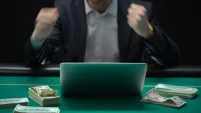 Dólares que aparecen en la tabla del casino, dinero que se besa del ganador feliz del juego online metrajes