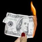 100 dólares que queimam-se em um fundo preto Fotos de Stock