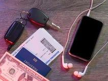 Dólares, teléfono móvil, pasaporte, llaves al coche, documento de embarque Imagen de archivo libre de regalías