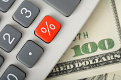 Dólares y calculadora con el botón rojo del por ciento Imagen de archivo