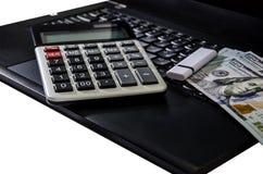 Dólares y calculadora en el teclado del ordenador portátil en el fondo blanco fotografía de archivo libre de regalías