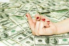 Dólares y dedo americanos imagen de archivo