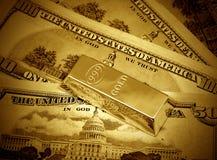 Dólares y lingote de oro imagen de archivo