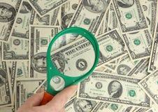Dólares y lupa Foto de archivo libre de regalías