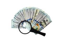 Dólares y lupa negra Imagenes de archivo