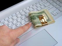 Dólares y ordenador Foto de archivo