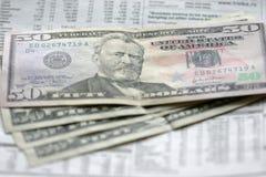 Dólares y periódico foto de archivo
