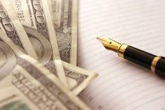 Dólares y pluma Foto de archivo libre de regalías