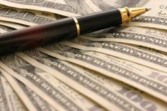 Dólares y pluma fotografía de archivo