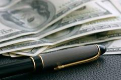 Dólares y pluma imagenes de archivo