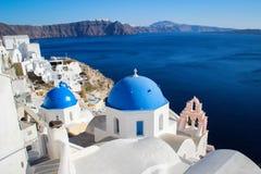 Dômes bleus et murs blancs de l'église sur l'île romantique célèbre de Santorini photos stock