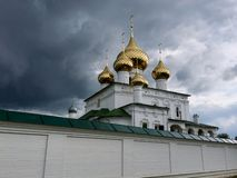 Dômes d'or de l'église orthodoxe et les murs blancs de temple dans la perspective d'un ciel gris orageux photo stock