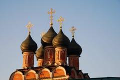Dômes noirs de l'église orthodoxe avec les croix d'or photographie stock libre de droits