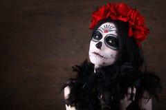 död dag halloween Den unga kvinnan i dag av den döda konsten för maskeringsskalleframsidan och steg Stranda av hår vänder mot in Arkivfoto
