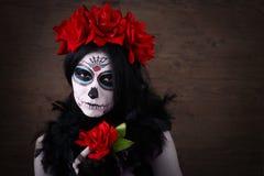 död dag halloween Den unga kvinnan i dag av den döda konsten för maskeringsskalleframsidan och steg Stranda av hår vänder mot in Royaltyfri Bild
