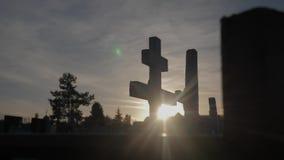 Dödlivbegrepp kyrkogården korsar livsstil för solljusglints bakifrån gravarna på den arga konturn för solnedgången stock video