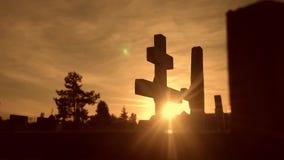 Dödlivbegrepp kyrkogården korsar solljus glints bakifrån gravarna på den arga konturlivsstilen för solnedgången stock video