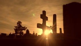 Dödlivbegrepp Kyrkogården korsar solljus glints bakifrån gravarna på den arga konturn för livsstilsolnedgången stock video