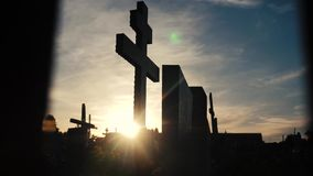Dödlivbegrepp kyrkogården korsar solljusglintslivsstil bakifrån gravarna på den arga konturn för solnedgången stock video