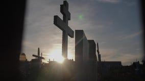 Dödlivbegrepp kyrkogården korsar solljuslivsstil glints bakifrån gravarna på den arga konturn för solnedgången stock video