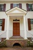 Dörröppning av det koloniala huset Arkivbild