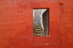 Dörröppning på den röda stenväggen som leder till trappuppgången inom en gammal byggnad i kloster av Santa Catalina, Arequipa, Pe royaltyfria bilder