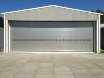 Dörr för rullningsslutare av den stora garagelageringången med det konkreta blockerade golvet, branschbyggnadsbakgrund med blå hi royaltyfri bild