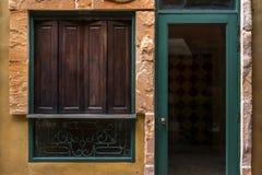 Dörr för träfönster och för grönt exponeringsglas på den gula väggen Arkivbild
