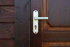 Dörr-handtag för gul metall på trädörrcloseupen Arkivbild