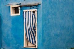 Dörr med den blåa och vita randiga gardinen och det lilla fyrkantiga fönstret arkivbild