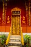 Dörr- och väggmålningen Buddistisk tempel med guld Luang Prabang laos Royaltyfri Foto