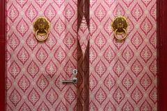 Dörrarna av en av korridorerna av Wat Mahathat i Bangkok, Thailand, täcktes med ett rött tyg som dekorerades med guld- modeller arkivfoton