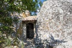 Dörrarna till huset i vaggar enorm sten i förgrunden royaltyfri fotografi