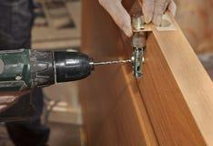 Dörrbeslaget, installerar deadboltlåset, borrad hol för den elektriska drillborren arkivfoton