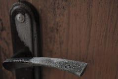 Dörrhandtaget täckas med vit frost arkivfoton