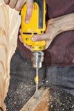 Dörrknopp som installerar genom att använda den gula maktdrillborren, sågspån som flyger a Arkivfoton