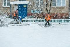 dörrvakten för två män i overaller skyfflar en bana framme av huset från snön under ett snöfall royaltyfri fotografi