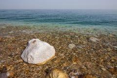 Dött havsvatten och stenar som täckas av den salta kristallen arkivbild