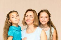 döttrar henne moder två 3 flickor för kamerasoffafamilj se sitting för orange stående för moder deras beträffande där Royaltyfri Foto