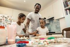 Döttrar och deras fader som tycker om att laga mat i köket royaltyfri foto