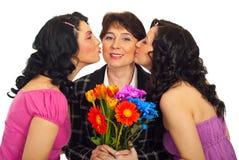 döttrar som kysser modern Arkivfoton