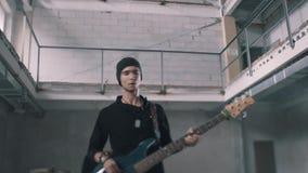 Dúo instrumental fresco Guitarrista y batería bajos en el fondo almacen de metraje de vídeo