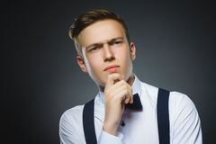 Dúvida, expressão e conceito dos povos - menino que pensa sobre o fundo cinzento Fotos de Stock Royalty Free