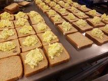 Dúzias de sanduíches da salada do ovo na tabela do metal na cozinha de sopa, alimentando o com fome fotografia de stock