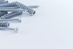 Dübel-Anschlussstecker und Schrauben am weißen Hintergrund Stockfoto