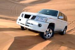 Düne, die in einer Nissan-Patrouille heftig schlägt lizenzfreie stockfotos