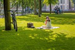 Dünn gekleidete junge Frau schaut im Park auf ihrem Smartphone Stockfoto